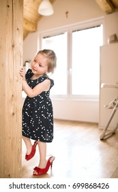 Cute little girl in dress and red high heels at home.