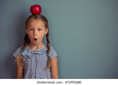 Cute little girl in dress is showing surprise, looking at camera and smiling, standing with red apple on her head on gray background
