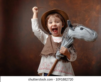 Cute little girl dressed like a cowboy playing with a homemade horse. Expressive facial expressions. Copy space for your text.
