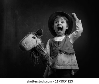 Cute little girl dressed like a cowboy playing with a homemade horse. Black and white.