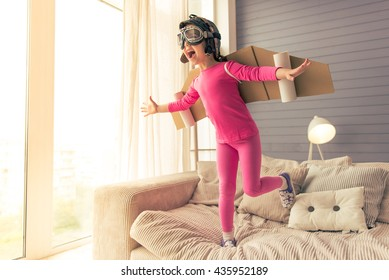 Cute little girl dressed like a pilot with toy wings is laughing while playing at home
