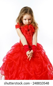 Cute little girl dressed in red posing in studio, isolated on white