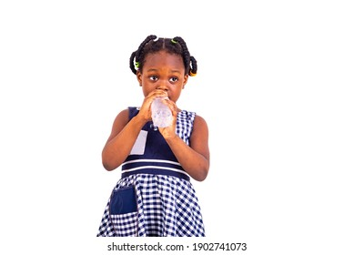 cute little girl dressed in school clothes drinking mineral water from plastic bottle.