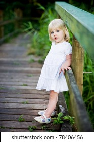 A cute little girl dressed in white leaning against the side of a boardwalk.