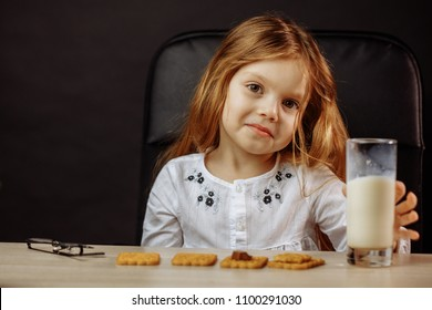Cute little girl drinking fresh organic milk with cookies at Dady s office. Healthy nutrition for small children.