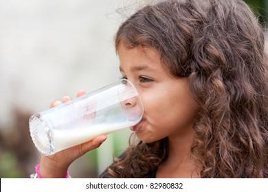 Cute little girl drinking a glass of milk