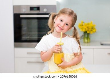 Cute little girl drinking juice and smiling at home.