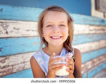 Cute little girl is drinking milk outdoors.