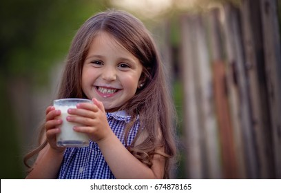 Cute little girl is drinking milk in the countryside