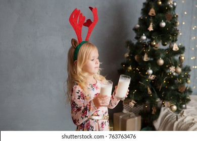 Cute little girl drinking milk and eating delicious cookie near Christmas at home. Christmas time.  Happy Christmas holidays!