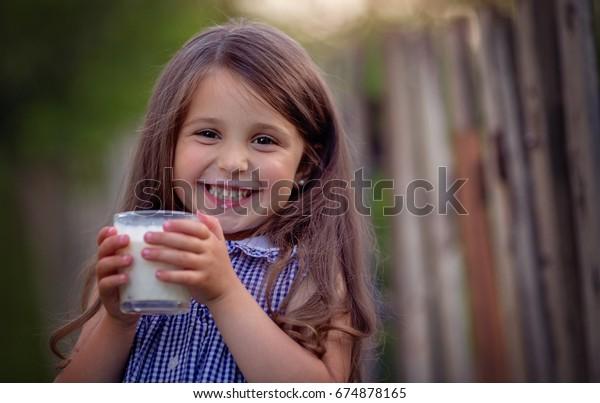 La Petite Fille Mignonne Boit Du Photo De Stock Modifiable 674878165