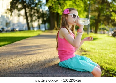 Cute little girl drinking water on hot summer day. Child holding a bottle ot water.