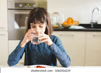 Cute little girl drinking water during lunch time in the kitchen at home