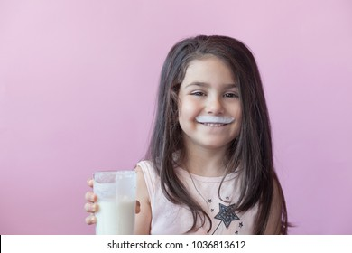 Cute little girl drinking yogurt. Whiskers from yogurt.