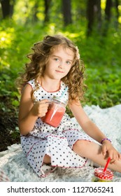 Cute little girl drinks healthy smoothie with straw in a jar mug against the background of greenery outdoor.  Happiness summer weekend concept.