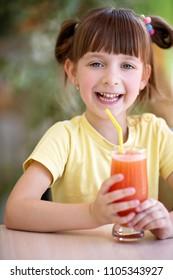 Cute little girl drinks juice using drinking straw