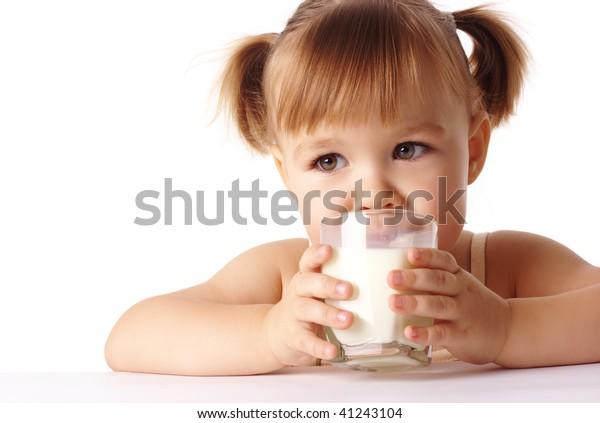 Cute little girl drinks milk, isolated over white