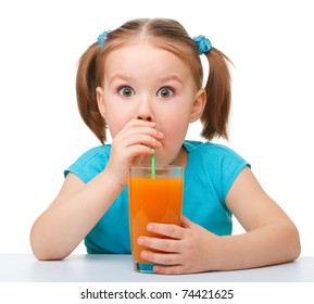 Cute little girl drinks orange juice using drinking straw and making big eyes, isolated over white