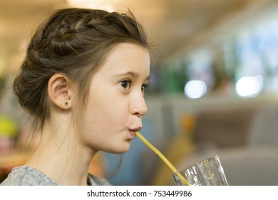 Cute little girl drinks from the straw