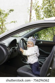 Cute little girl driving car. Child sitting in big car