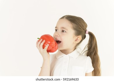Cute little girl eating bell pepper on white background. Nutrition. Healthy food concept.