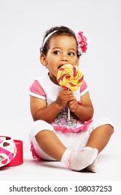 Cute little girl eating a big lollipop
