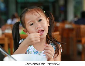 Cute little girl eating breakfast in the restaurant at the morning.