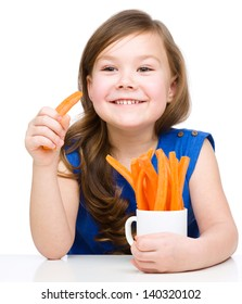 Cute little girl is eating carrot, isolated over white