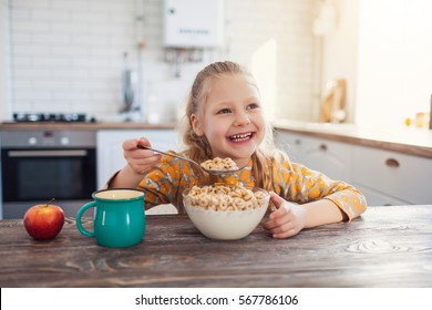 cute little girl eating cereal with the milk at home