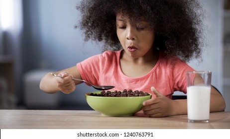 Cute little girl eating chocolate cornflakes for breakfast, risk of diabetes