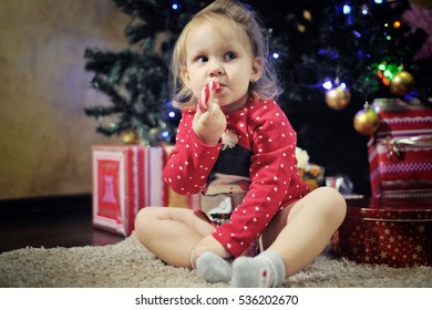 Cute little girl eating Christmas candy cane