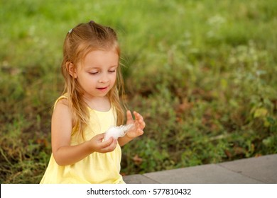 Cute little girl eating cotton candy. A walk in the summer park. Summer vacation. Outdoor Activities.
