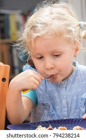 Cute little girl eating dessert from the plate with fork