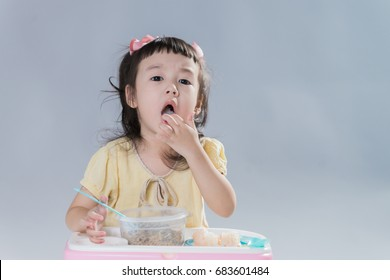 Cute little girl eating food in gray background.