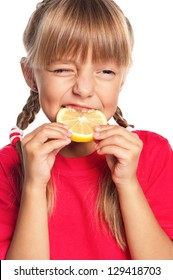 Cute little girl eating fresh lemon isolated on white background