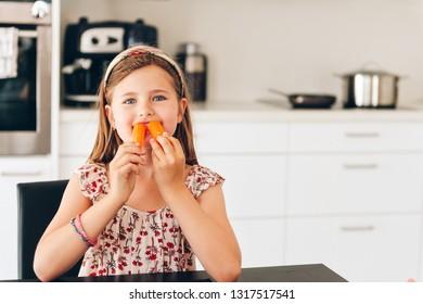 Cute little girl eating fresh carrot in white kitchen, vitamins nutrition for children