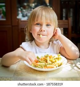 Cute little girl eating Fusilli