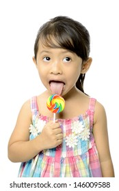 Cute little girl eating her lollipop isolated over white background