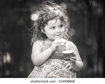 Cute little girl eating ice cream in the park