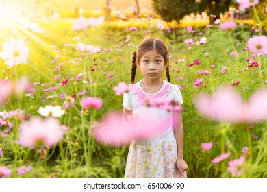 Cute little girl eating ice cream  in the field of pink flowers at sunlight