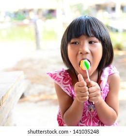 cute little girl eating a lollipop in summertime