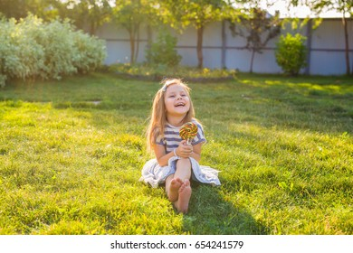 cute little girl eating a lollipop on the grass in summertime.