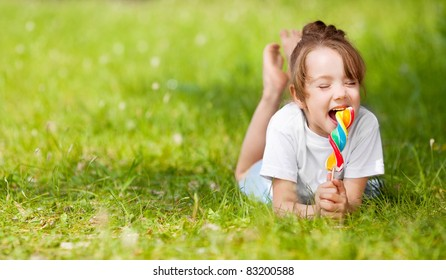 cute little girl eating a lollipop on the grass in summertime