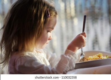 Cute little girl eating pasta outdoors