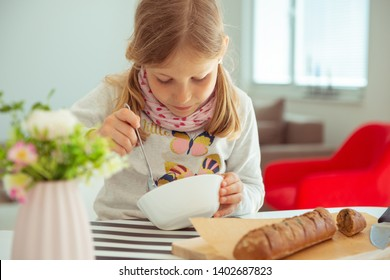 Cute little girl eating soup with whole grain bread in bright living room at home