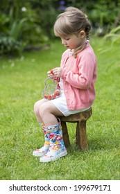 Cute little girl eating strawberries in the garden