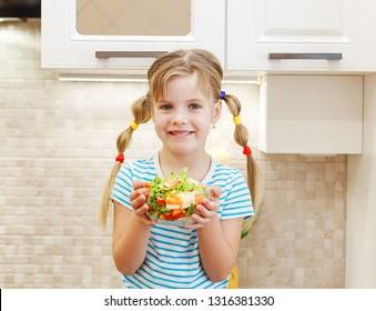 Cute little girl eating vegetables in kitchen. Child on kitchen eating salad.