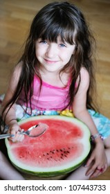 Cute little girl eating watermelon with a spoon on the floor
