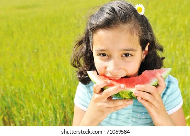 cute little girl eating watermelon on the grass in summertime