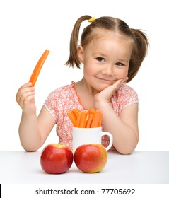 Cute little girl eats carrot and apples, isolated over white